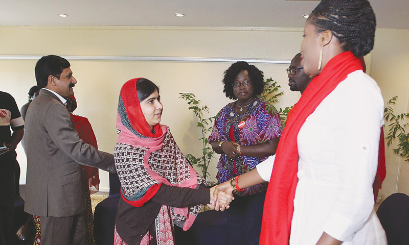 Abuja (Nigeria): Malala Yousafzai shakes hands as she is welcomed during a meeting with leaders of the BringBackOurGirls Abuja campaign group as she arrived to attend a meeting of the group on Sunday.—Reuters
