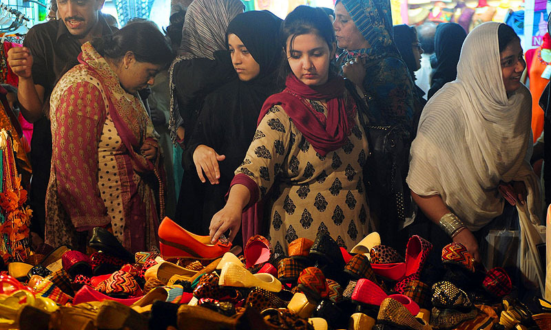 Women buy shoes at a market ahead of Eid. — File photo