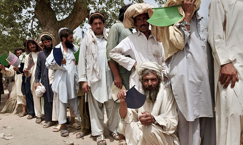 This file photo taken on July 13, 2014 shows internally displaced Pakistani civilians queuing outside the World Food Programme food distribution centre in Bannu. – AFP Photo