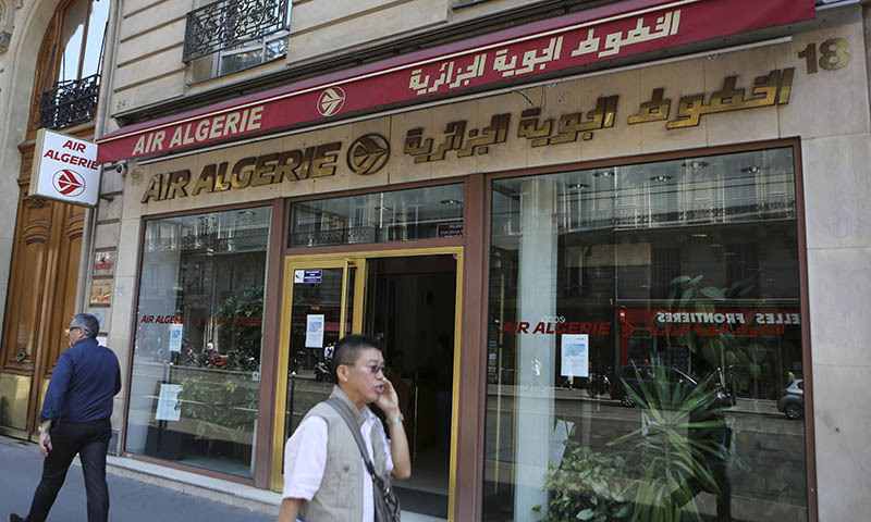 Passersby walk past the Air Algerie company office, on the Opera Avenue in Paris Thursday July 24, 2014. An Air Algerie flight crashed on Thursday en route from Ouagadougou in Burkina Faso to Algiers with 110 passengers on board. Almost half of the passengers were French citizens, an airline official said. — Photo by AP