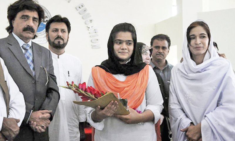 Top position holder in the annual Intermediate Examination Omaima Nazar  receiving her prize from the chairman of Abbottabad board on Thursday. — Online