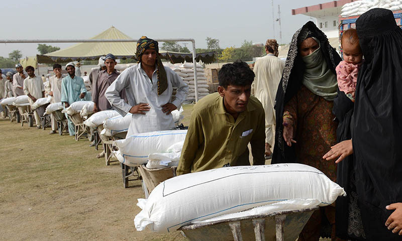 Workers prepare to distribute food supplies to civilians, fleeing a military operation in the North Waziristan tribal agency, at a World Food Programme aid distribution centre in Bannu. — File photo by AFP