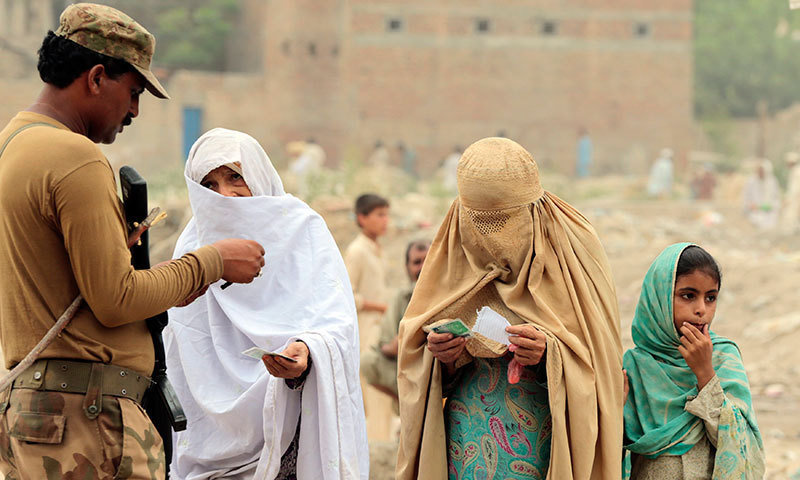 Internally displaced women beg a soldier to allow them to enter a food distribution centre set up in a sports stadium in Bannu, in northwest Pakistan. — Photo by Reuters