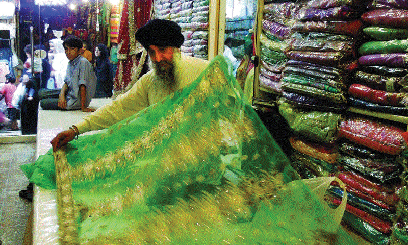 Saroop Singh display a dress at his shop in Moti Bazaar.