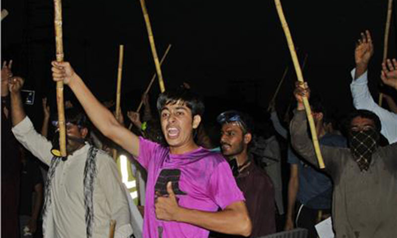 Supporters of Pakistan Awami Tehreek chant slogans as they wave sticks during a protest in Lahore.— Photo by Reuters