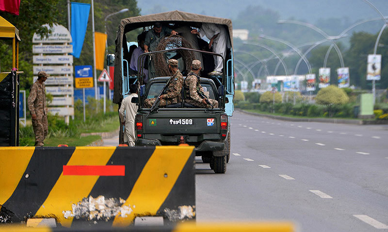 Pakistani soldiers prepare to roll out barbed wire from a vehicle as they patrol in a 'red zone' area of Islamabad on August 13, 2014. — Photo by AFP