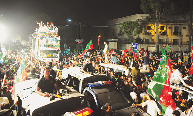LAHORE: A truck (left) carrying PTI chief Imran Khan and other leaders heading a march on Islamabad from here on Thursday.—M. Arif/White Star