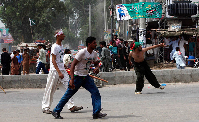 Supporters of PTI hurl stones in reaction to residents throwing stones at the participants of Azadi March, Gujranwala, August 15. — Photo by Reuters