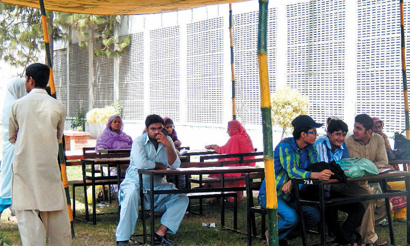 SAHIWAL: Candidates are sitting under a tent in front of the secrecy branch for want of space in the BISE building.—Dawn