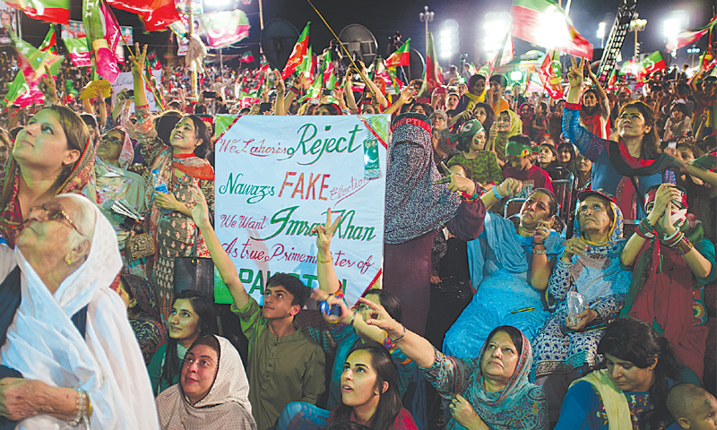 PTI supporters listen to Imran Khan's speech at the sit-in here on Saturday. — Photo by AP