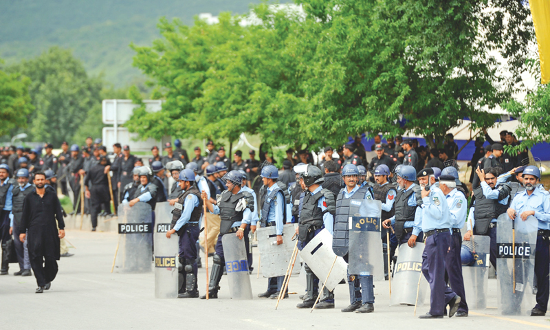 Police personnel stand alert near the sites of the sit-ins in Islamabad on Monday. — Photo by Tanveer Shahzad
