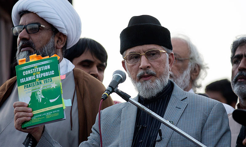 Dr Tahirul Qadri shows a copy of Pakistan's constitution which he claims it was violated by rulers, during a sit-in protest near the parliament building in Islamabad on Thursday. – AP Photo