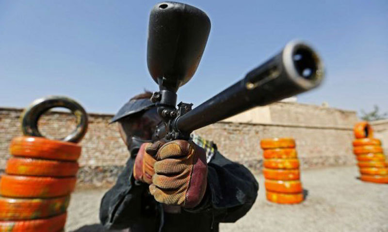 A man holds up his gas-powered gun while playing paintball in Kabul, Afghanistan. – Photo by AP