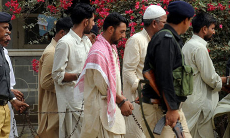 Pakistani policemen escort arrested hand-cuffed paramilitary soldiers and a civilian to an anti-terrorism court in Karachi. — AFP file photo