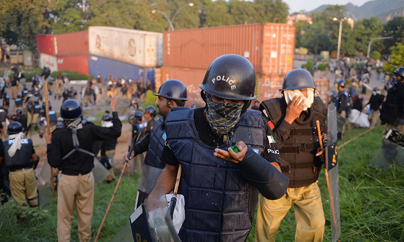 Pakistani riot police protect themselves from tear gas during clashes — AFP Photo