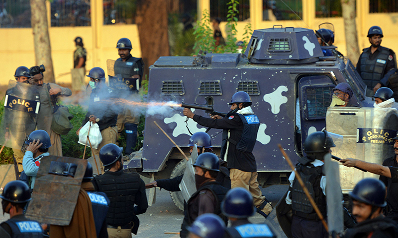 A policeman (C) fires a tear gas shell toward supporters of Imran Khan and Canadian cleric Tahir ul Qadri during clashes near the prime minister's residence in Islamabad on August 31, 2014. — AFP