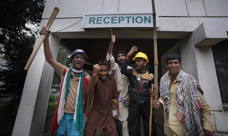 Protesters hold sticks and chant slogans after intruding the state television building in Islamabad, Sept. 1, 2014. —AP photo