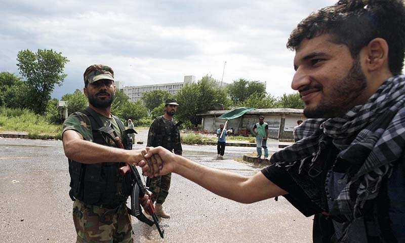 A supporter (R) of PAT chief Tahirul Qadri, shakes hands with a soldier from the Pakistan Army, during the Revolution March towards the prime minister's house in Islamabad September 1, 2014.— Photo by Reuters