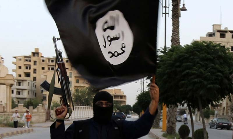 A member of the Islamic State in Iraq and the Levant (ISIL) waves an ISIL flag. — File photo by Reuters
