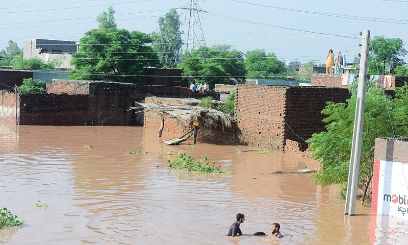 Families took to the rooftop of their houses after the floodwaters surged through a village along the Wazirabad-Gujrat bypass on Sunday.  —Tariq Mahmood / White Star