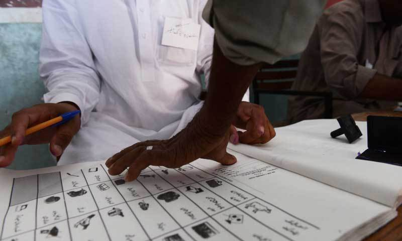 The image shows a citizen at a polling station casting a thumb impression during the process of voting. — File photo