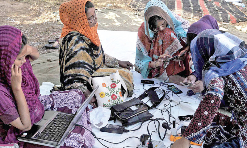 Women protesters charge their mobile phones and laptops at the sit-in venue in Islamabad. — Photo by Ishaque Chaudhry