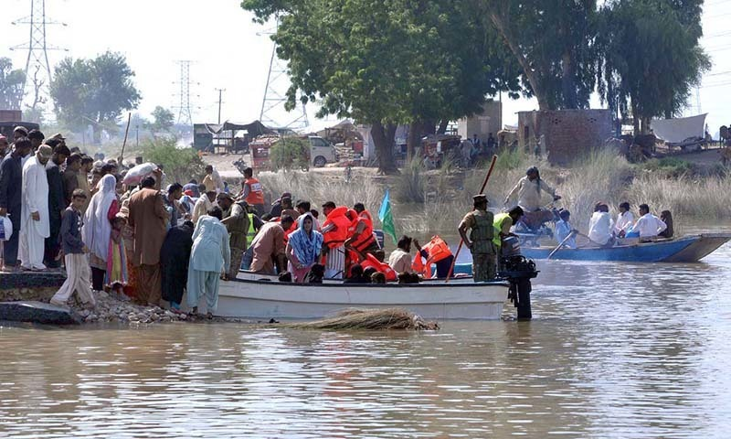 Pakistan Army soldier helping people to cross the flood water through boat at Sher Shah to reach the other side Muzaffargarh.— Photo by APP