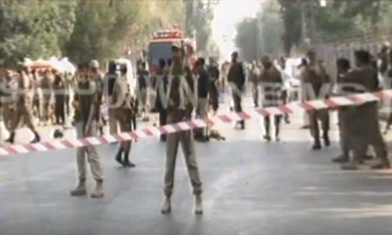 Security personnel cordon off the site of the explosion on Peshawar's Saddar Road. — DawnNews screengrab