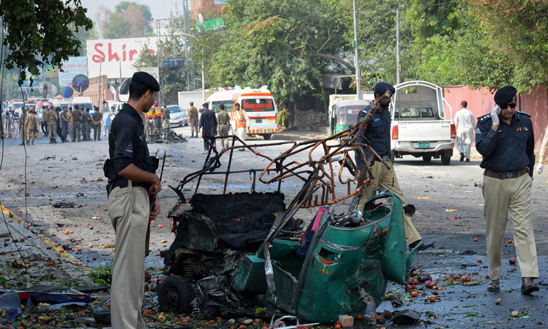 Police officials stand beside a mangled auto-rickshaw at the site of a suicide bomb attack in Peshawar on September 23, 2014.— Photo by AFP