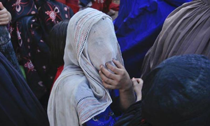 An internally displaced girl from Bara looks through a scarf covering her face while sitting amid other women waiting to be registered at the camp.— Reuters file photo