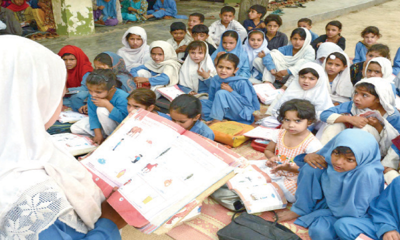 Students study in the open at a school in Peshawar. — Dawn