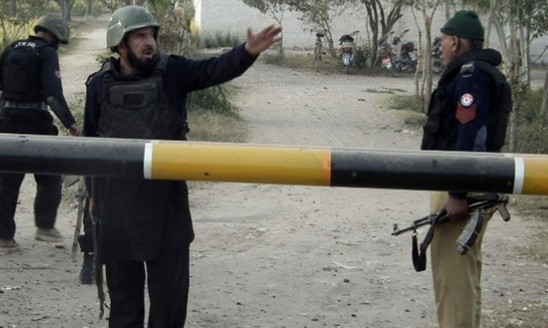 This picture shows security personnel standing on alert at a street in Hangu. — File photo/Online