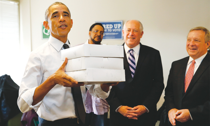 Chicago: US President Barack Obama carries boxes of pastries into a campaign office here on Monday. With Obama is Illinois Governor Pat Quinn (centre) and Senator Dick Durbin who are both running for re-election.—Reuters