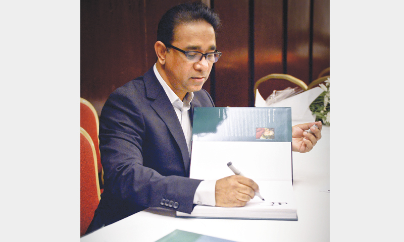 RAFIQ Azam signs copies of his book at the launch.—White Star