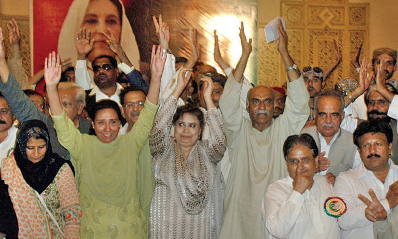 Nahid Khan and Dr Safdar Abbasi wave to workers during  a convention at Aiwan-i-Iqbal. – INP