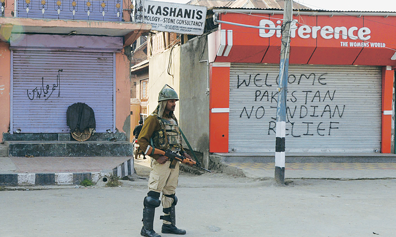SRINAGAR: An Indian paramilitary soldier stands guard on a deserted street during a strike here on Monday. —AFP