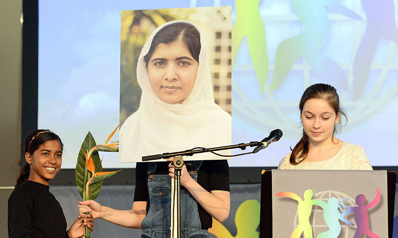 A girl holds a picture of Malala Yousafzai of Pakistan, winner of the 2014 World's Children's Prize for the Rights of the Child, during a press conference in Stockholm. -AFP Photo