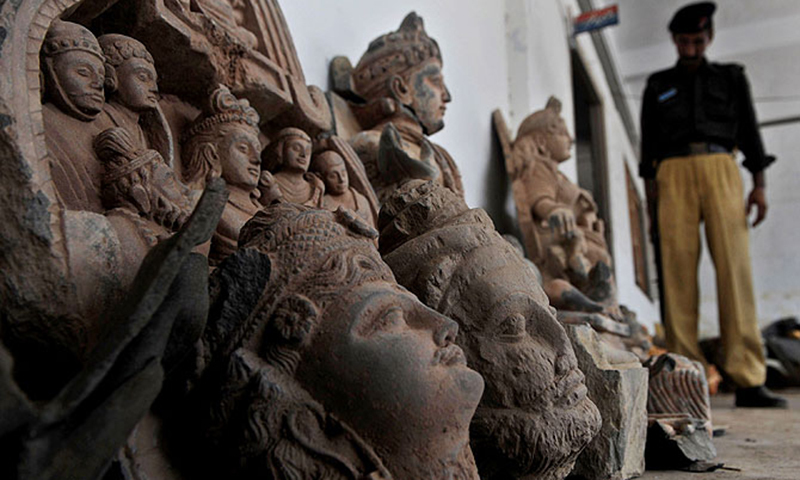 This picture shows a police official inspecting seized ancient statues. — File photo/AFP