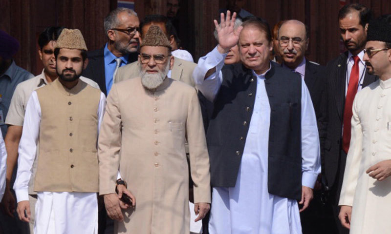 Pakistani Prime Minister Nawaz Sharif  waves as he walks with Syed Ahmed Bukhari, the Shahi Imam of the Jama Masjid, during his visit to in New Delhi on May 27, 2014. -AFP/File Photo