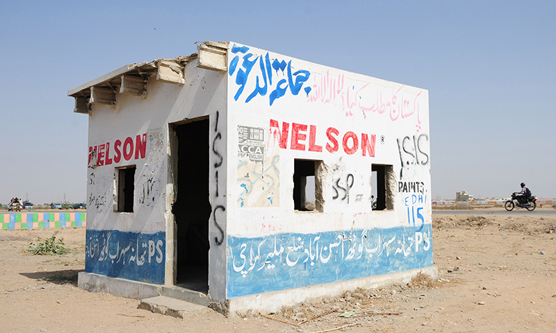 """This picture shows motorists driving past an empty police check post with graffiti which reads as """"ISIS"""" along a street on the outskirts of Karachi. — Photo by AFP"""