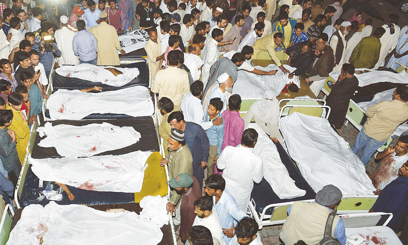 RELATIVES gather around bodies of victims in a hospital after the suicide bomb attack near the Wagah border on Sunday.—AFP