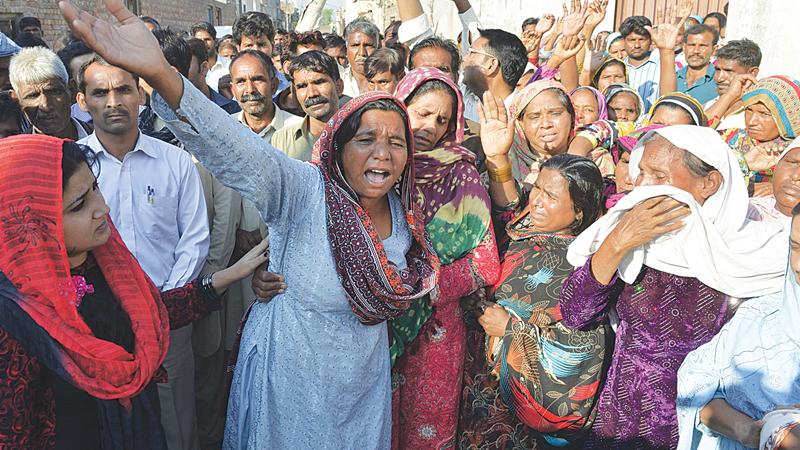 RELATIVES and friends mourn the death of the Christian couple in Kot Radha Kishan on Wednesday.—AFP