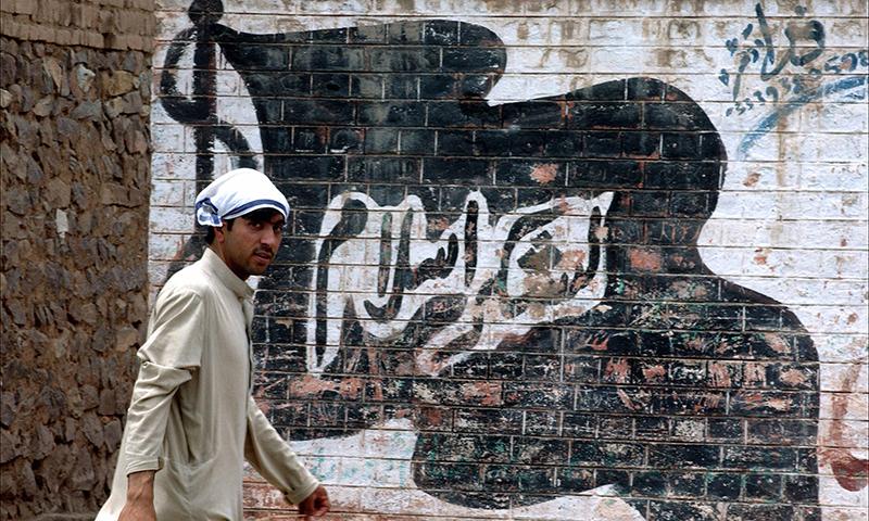 Эта картина показывает человека, идущего мимо стены окрашены с флагом запрещенной повстанческой группы Лашкар-и-Ислам.  - AFP / File