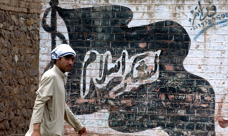 This picture shows a man walking past a wall painted with the flag of the outlawed group Lashkar-i-Islam. — AFP/File
