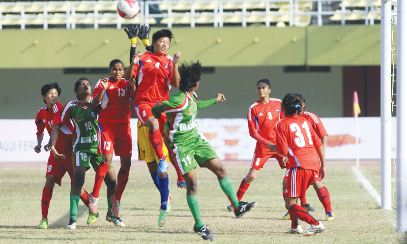 Nepal's goalkeeper (obscured) tries to catch the ball under pressure during the SAFF Women's Championship semi-final  against Bangladesh on Wednesday.—Tanveer Shahzad/White Star