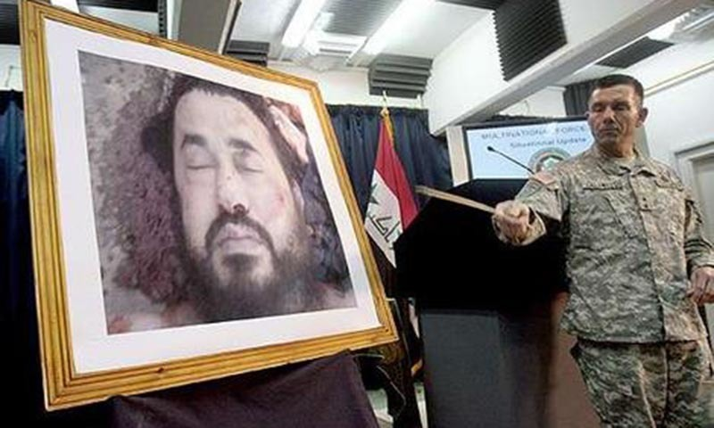 A US military officer shows a picture of the dead Abu Musab al-Zarqawi who was killed in a drone strike in June 2006.- AFP