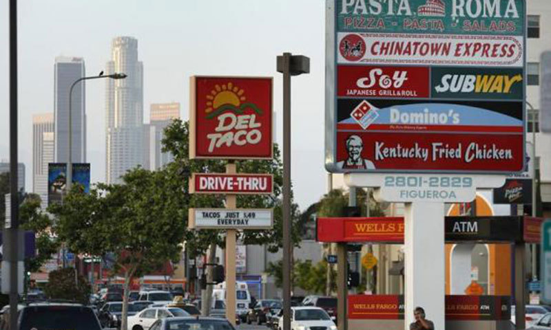 Signs Of Fast Food Restaurants Are Seen Along A Busy Street In Los Angeles California