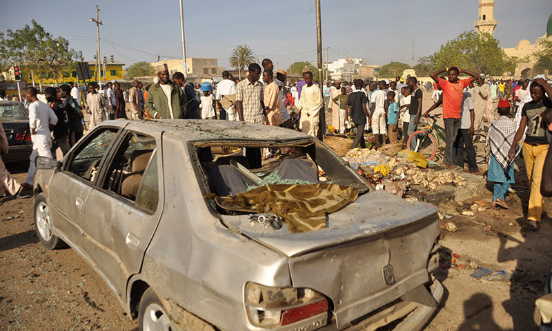 People gather at the site of a bomb explosion in Kano, Nigeria. -AP Photo