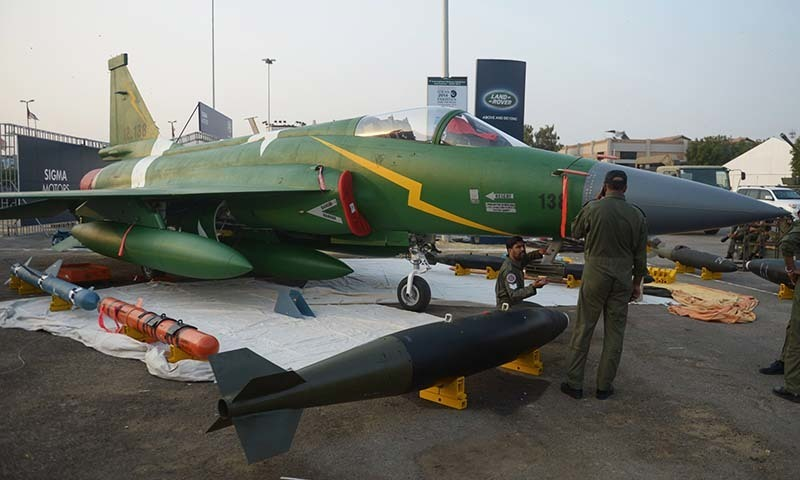 Personnel are pictured near a PAC JF-17 Thunder multirole combat aircraft, jointly developed by China and Pakistan, during preparations for the International Defence Exhibition and seminar (IDEAS) in Karachi on November 29, 2014. - AFP