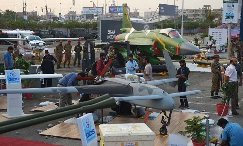 Officials prepare a locally-manufactured unmanned aerial vehicle for display as a PAC JF-17 Thunder multirole combat aircraft, jointly developed by China and Pakistan, is seen in background at right during preparations for the International Defence Exhibition and seminar (IDEAS) in Karachi on November 29, 2014. - AFP